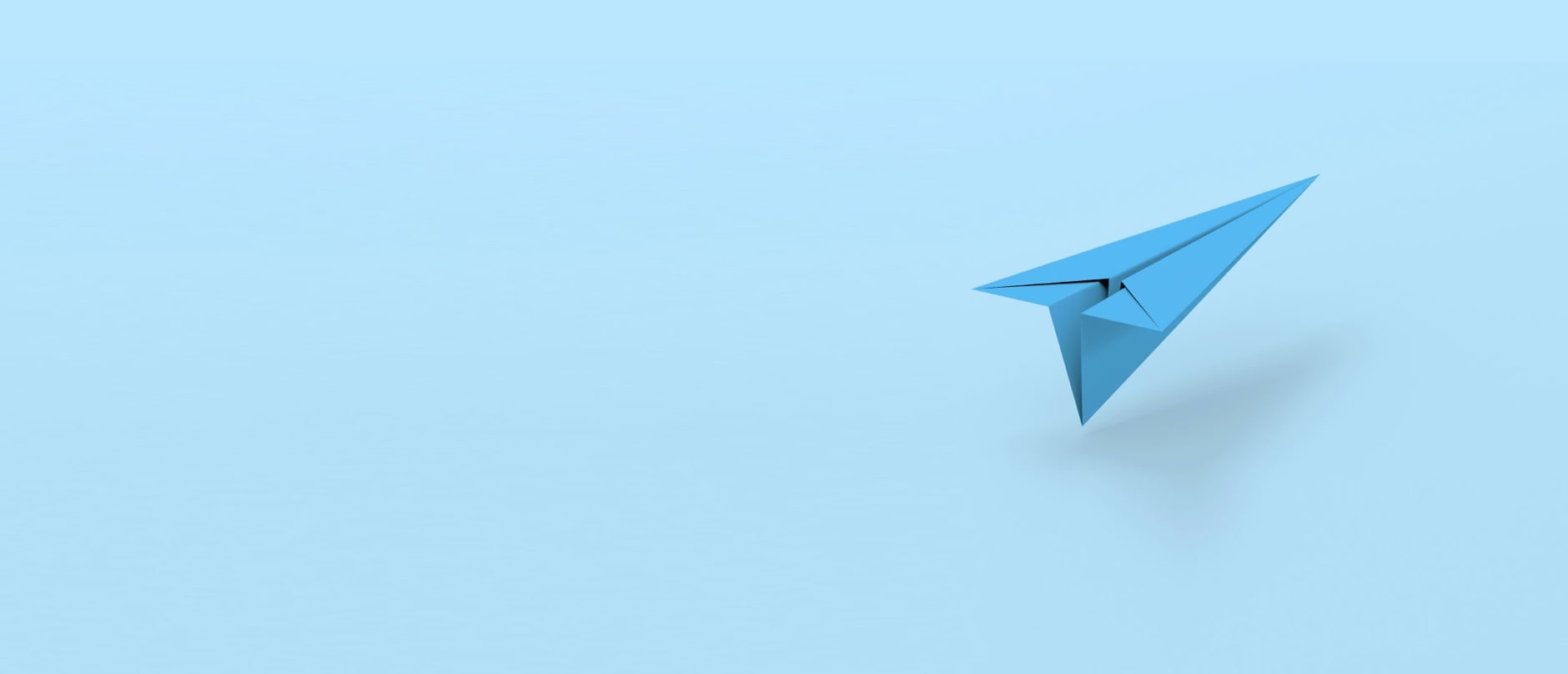 blue paper airplane on blue back drop