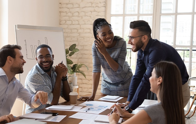 5 people laughing around a conference table