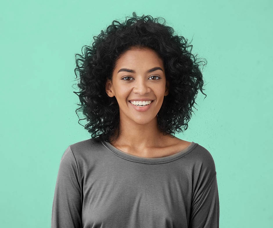 woman smilin on teal background