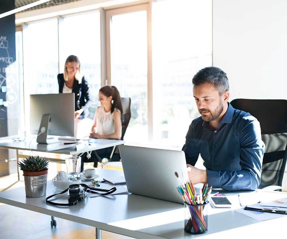 two people sitting at desk in an office enviroment