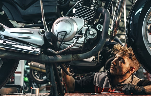 man working on motorcycle engine