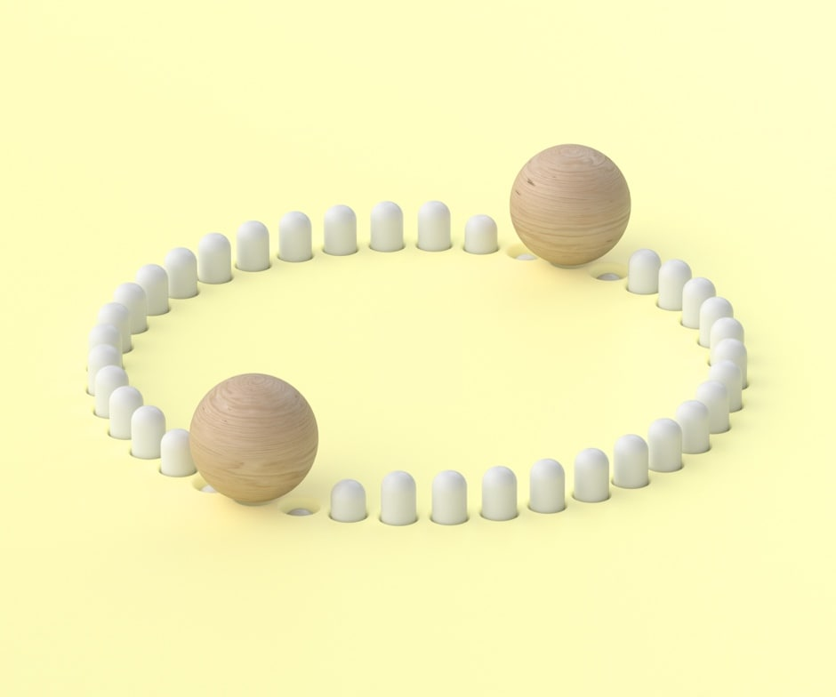 A circle of white cylinders with 2 wooden balls pushing down a few on opposite sides of the circle.