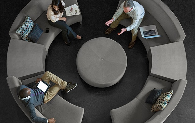 overhead view of people sitting on circular sectional with round centerpiece