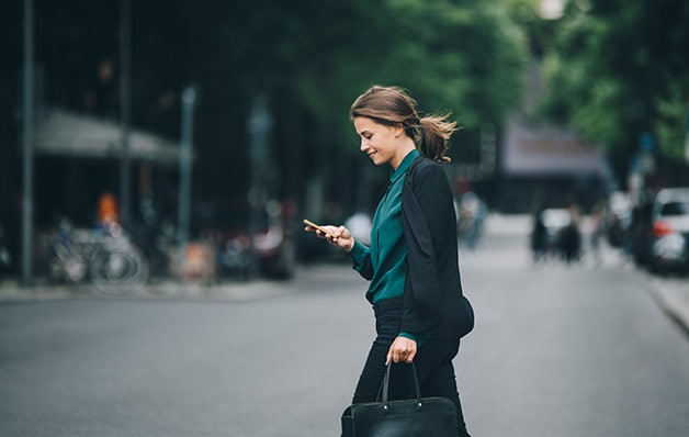 woman looking at phone while crossing the street