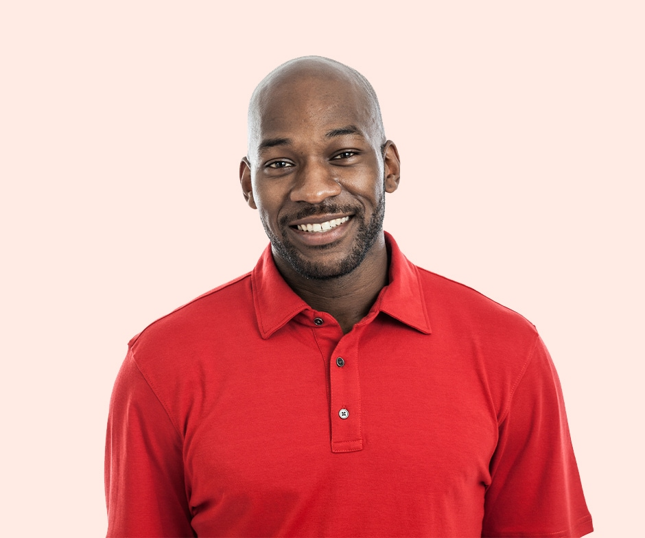 smiling guy in red shirt with peach background