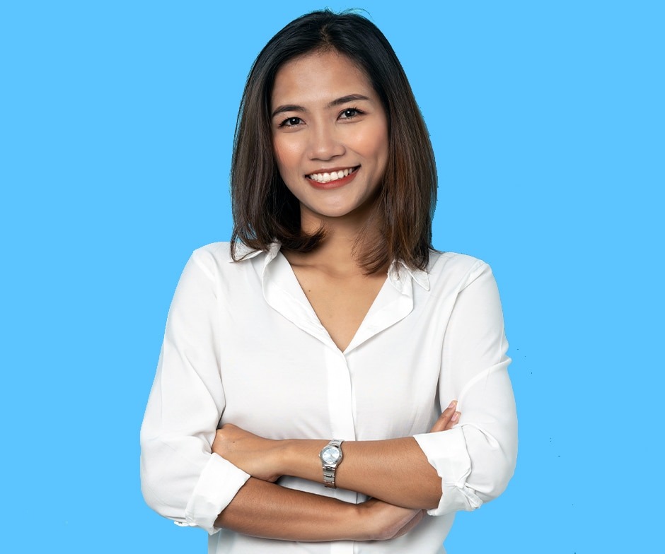 smiling lady wearing white shirt with arms crossed in front of blue background