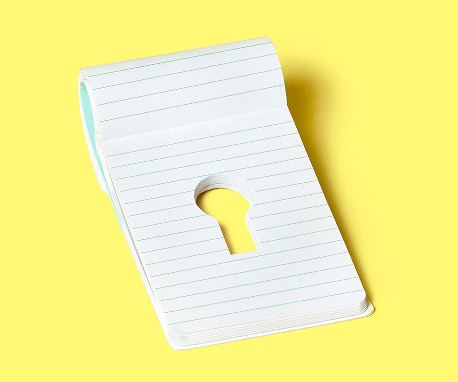 yellow background with small notepad with a keyhole cutout in the middle