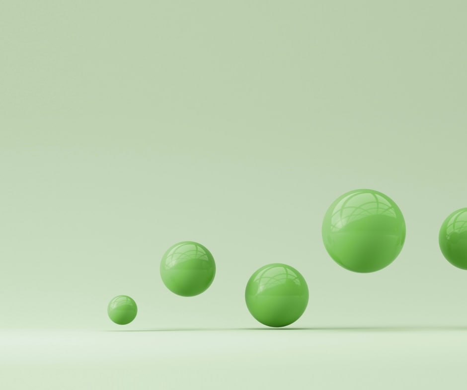 shiny green spheres bouncing onto light green background